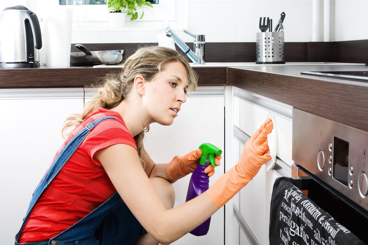 Young woman cleaning kitchen cabinets with a spray cleaner.