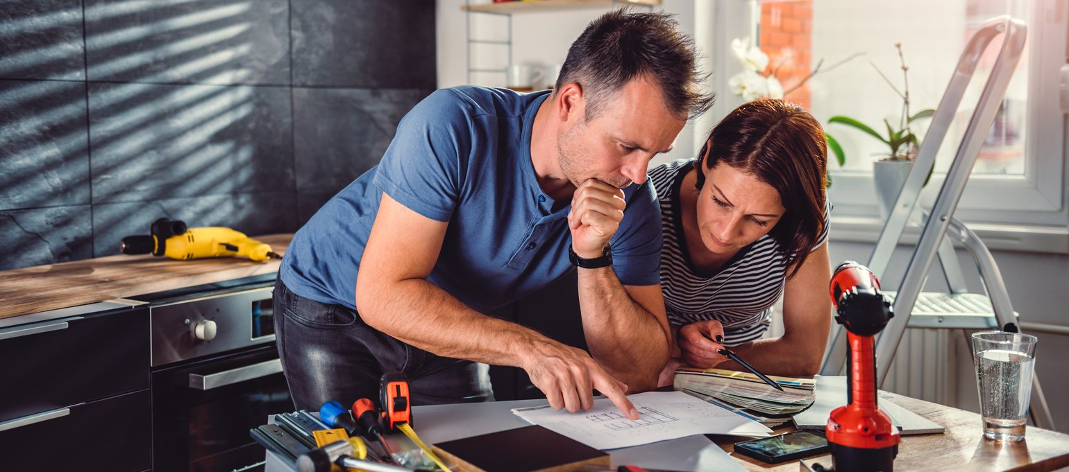 Couple looking at blueprints during kitchen renovation