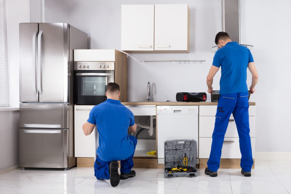 Two Men Checking Induction Stove And Sink Pipe